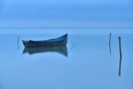 Lonely boat on big lake in the fog, blue hour before sunrise