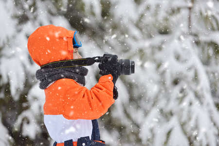 Happy kid with photo camera taking pictures in winter snowy day Stock Photo