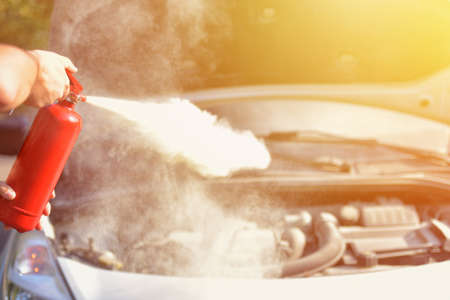 A man demonstrating how to use a fire extinguisher over a car engine Stockfoto