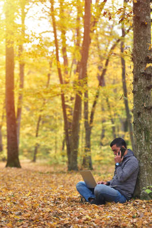 Man with laptop and smartphone in forest, autumn colors, sunset warm light