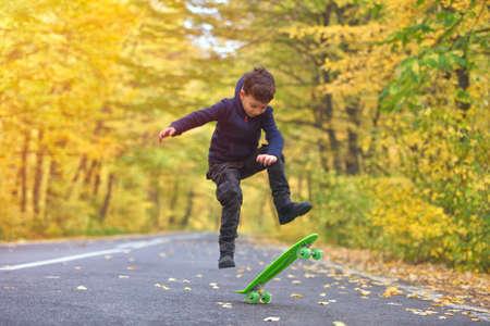 Kid skateboarder doing skateboard tricks in autumn environment