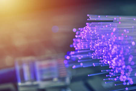 Fiber optics in magenta, close up with network and keyboard background, warm lens flare Stock fotó