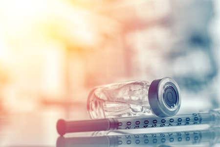 Primer plano de un frasco de medicina o gripe, botella de vacuna contra el sarampión con jeringa y aguja para inmunización en concepto de antecedentes médicos, medicina y drogas vintage Foto de archivo