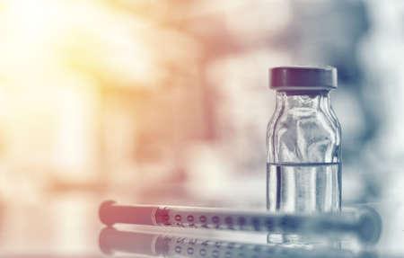 Primer plano de un frasco de medicina o gripe, botella de vacuna contra el sarampión con jeringa y aguja para inmunización en concepto de antecedentes médicos, medicina y drogas vintage