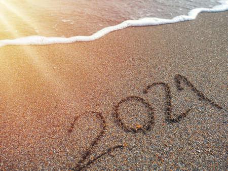 Year 2021 hand written on sandy beach in sunset warm lens flare Stok Fotoğraf - 123297910