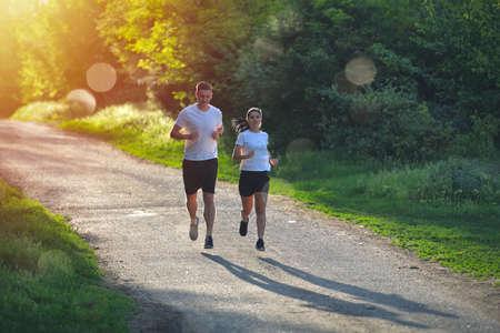 Giovani che fanno jogging e si allenano nella natura, nella luce calda dell'alba del mattino