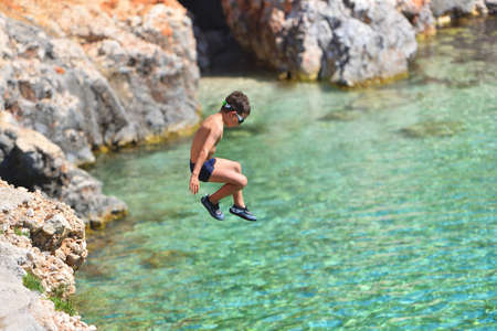 Little boy jumping off cliff into the ocean. Summer fun lifestyle. Brave kid