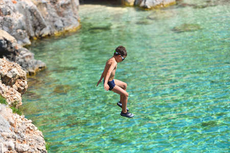 Little boy jumping off cliff into the ocean. Summer fun lifestyle. Brave kid Foto de archivo - 130818612