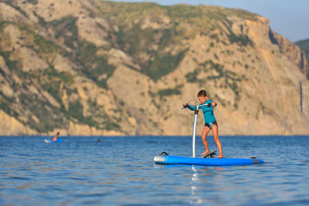 Happy active kid on a Hobie Stand Up Paddle board