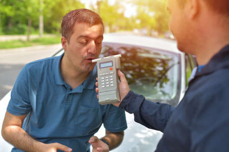 Driver due to being subject to test for alcohol content with use of breathalyzer Stok Fotoğraf