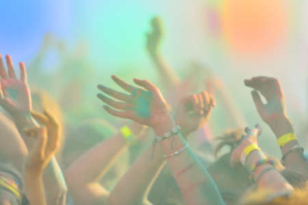 Defocused image of close-up with pople hands on running marathon, people covered with colored powder. Banco de Imagens
