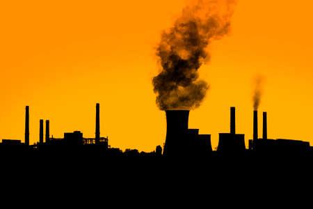 Dark harmful smoke from chimneys of power plant silhouette on sunset clear orange sky.