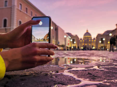 Young woman traveler tourist taking beautiful landscape photo of european sunset during holiday vacation Banco de Imagens