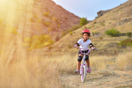 Happy kid girl of 7 years having fun in autumn park with a bicycle on beautiful fall day. Active child wearing bike helmet Banco de Imagens