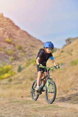 Happy kid boy of 7 years having fun in autumn park with a bicycle on beautiful fall day. Active child wearing bike helmet
