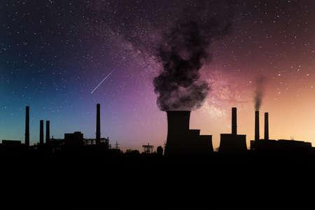 Dark harmful smoke from chimneys of power plant silhouette on night sky with milky way. Banco de Imagens