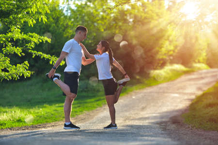 Young couple stretching legs on a road at the park Banco de Imagens