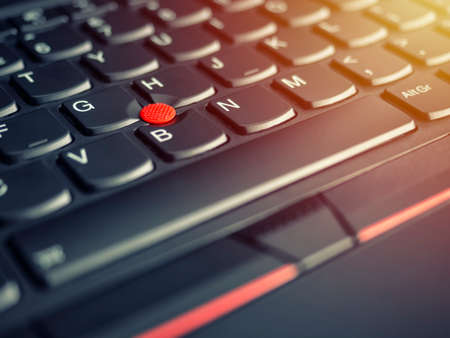 A close-up photo of the red pointing stick of on a laptop keyboard