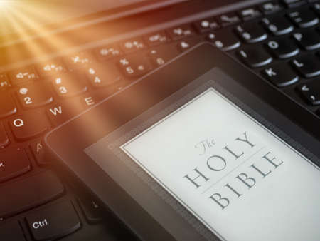 Close up of ebook reader with The Holy Bible on a laptop keyboard, with sun rays light concept