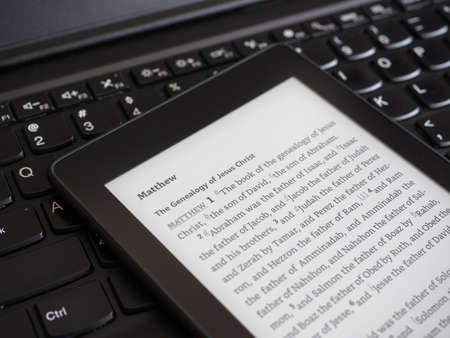 Close up of ebook reader with The Holy Bible on a laptop keyboard 免版税图像