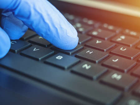 Online quarantine training. Remote online work. Coronovirus. Epidemic. Hands in protective medical gloves are typing on the keyboard.