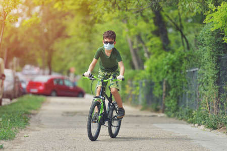 Happy kid having fun near home with a bicycle on beautiful spring day wearing protection mask for coronavirus Covid-19 pandemic virus