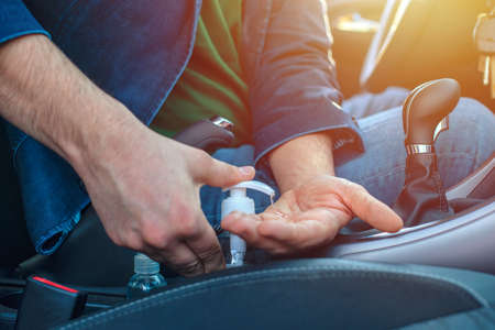 Man sitting in the car disinfect his hands to avoid coronavirus infection. Close-up on hands. Man using hand sanitizer in the car. 免版税图像