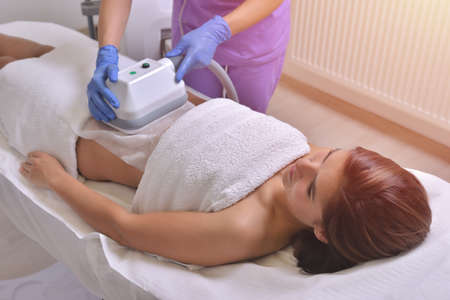 Beautiful young woman getting cryolipolyse treatment in cosmetic cabinet Imagens
