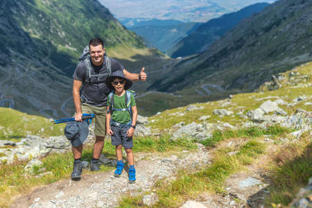 Father and son on top of the mountain, hiking with bakpacks in sunny day. Mountain scenery