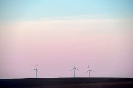 Eolian turbines park at sunet, warm light. Wind power concept Imagens