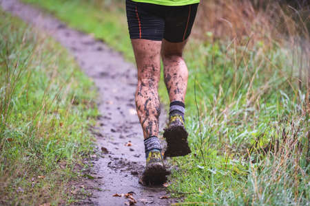 Athlete runner in forest trail in rain, with muddy legs
