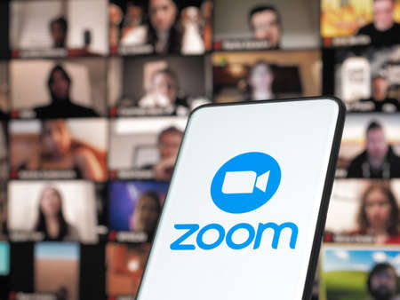 11 January 202 - Bucharest, Romania: Smartphone starting Zoom Cloud Meetings app with meeting on a background monitor
