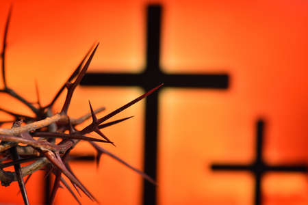 Crown of thorns of Jesus Christ against silhouette of catholic cross at sunset background Imagens
