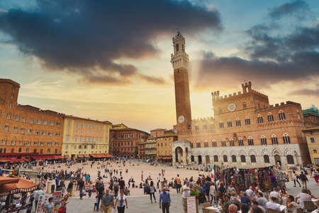 Siena, Italy - September 11, 2019: Sunset over tourists inside Piazza del Campo in a cloudy day, Siena, region of Tuscany, Italy Editorial
