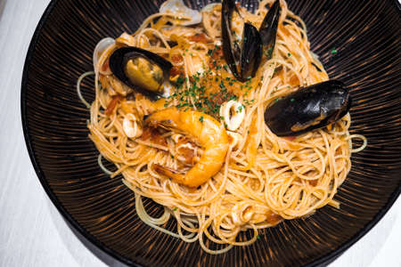 High angle view of large dish of pasta with various kinds of seafood. 免版税图像
