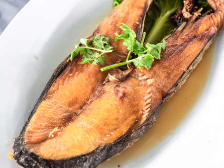 Deep fried king mackerel sprinkled with coriander sprigs.