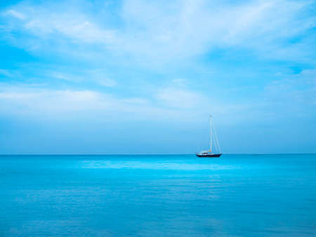 Turquoise blue sea with blue sky and a visible saling boat in distance, floating on horizon. Stock Photo