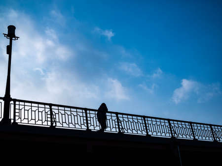 Silhouette of man walking on bridge with visible fence, light pole, and lightly cloudy blue sky.