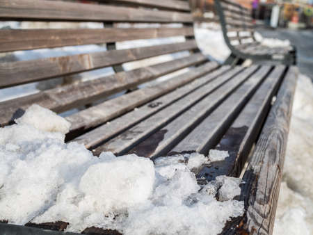 Closeup​ shot​ of​ left​over​ snow on​ wooden​ bench.