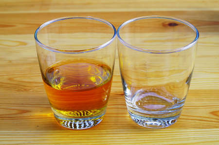 emty: An empty glass and glass with drink on a wooden table Stock Photo
