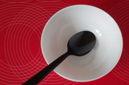 red tablecloth: black spoon in a white bowl on a red tablecloth
