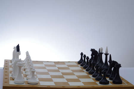 chess board: Chess pieces on the board in a white room