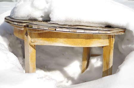 Old wooden round table under melting show