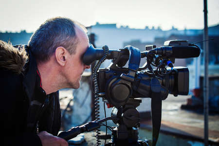 filmacion: camarógrafo con su cámara de vídeo de tiro al aire libre en la ciudad en los techos Foto de archivo
