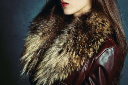leather coat: woman wearing leather jacket with fur, profile, studio shot