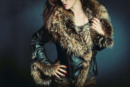 fur: young woman wearing leather jacket with fur studio shot Stock Photo