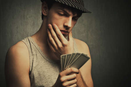 tank top: young man in tank top and hat watch his poker cards, studio shot