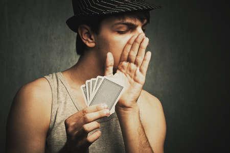 whisper: poker player whisper to someone holding cards in hand , studio shot Stock Photo