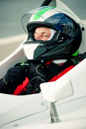 race car driver: driver in race car adjust helmet before race