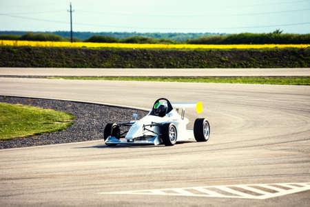 razas de personas: coche de carreras unidad de hombre en una pista Foto de archivo
